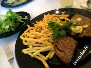 Steak mit Kräuterbutter auf Pommes mit Blattsalat