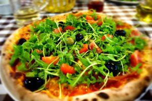 Pizza mit Rohschinken, Rucola & Oliven